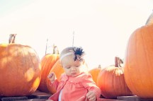 Baby sitting with pumpkins